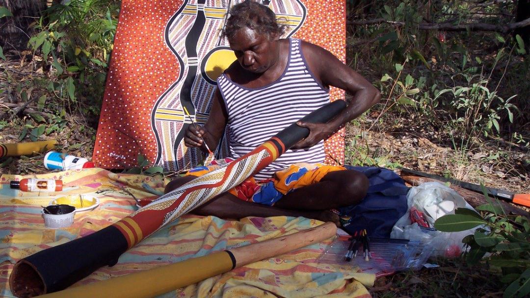 Une femme Aborigène peint un didgeridoo traditionnel