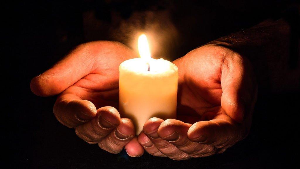 Deux mains qui tiennent une bougie allumée dans le noir.